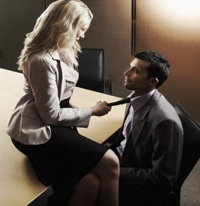 Businesswoman pulling on colleague's necktie --- Image by © Serge Kozak/Corbis